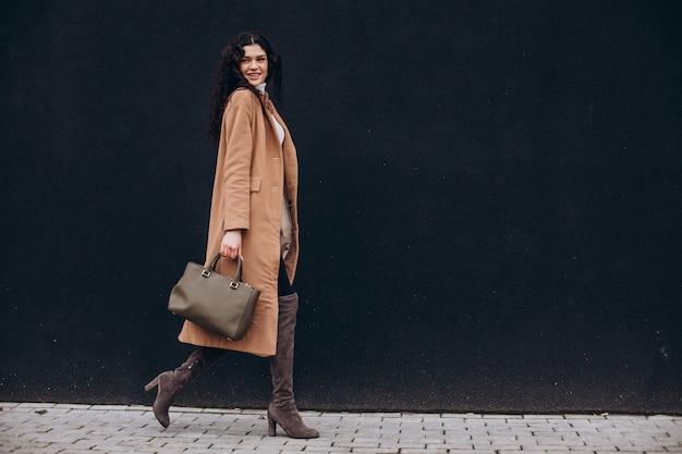 Mujer joven en abrigo beige caminando al aire libre sobre fondo de pared negra