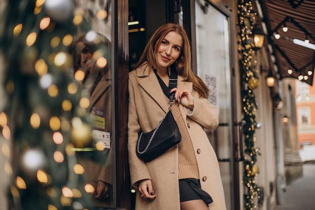 Mujer joven en abrigo beige caminando por la calle en navidad