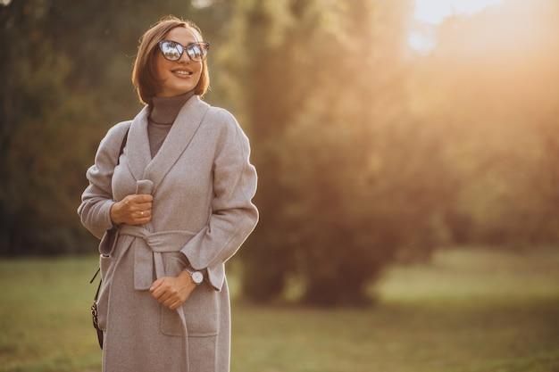 Mujer joven en abrigo gris caminando en un parque de otoño
