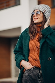 Mujer joven en abrigo en invierno por la casa