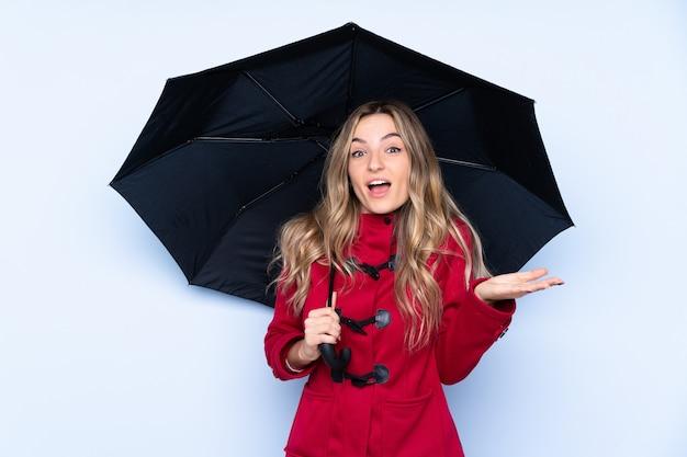 Mujer joven con abrigo de invierno y sosteniendo un paraguas con expresión facial sorprendida