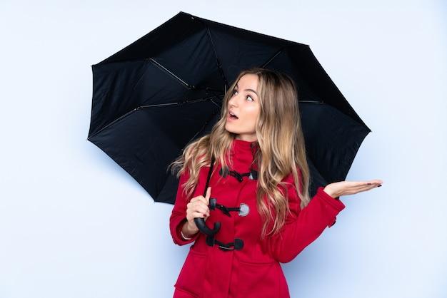 Mujer joven con abrigo de invierno y sosteniendo un paraguas con expresión facial sorpresa