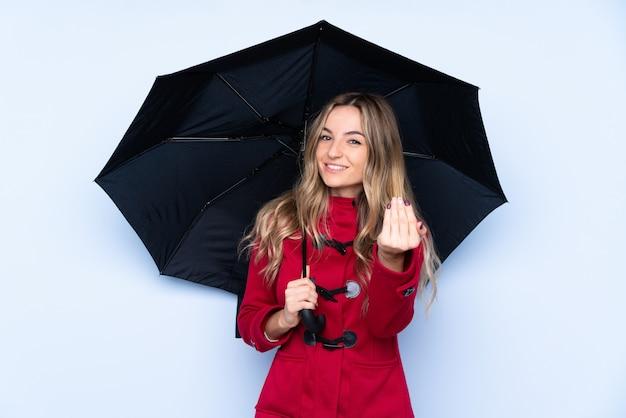Mujer joven con abrigo de invierno y sosteniendo un paraguas invitando a venir con la mano. feliz de que hayas venido