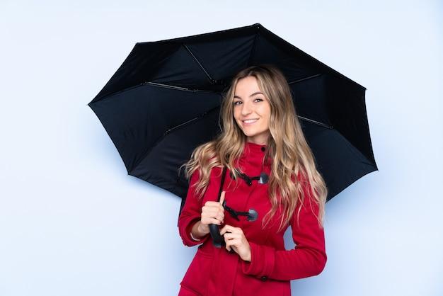 Mujer joven con abrigo de invierno y sosteniendo un paraguas sonriendo mucho
