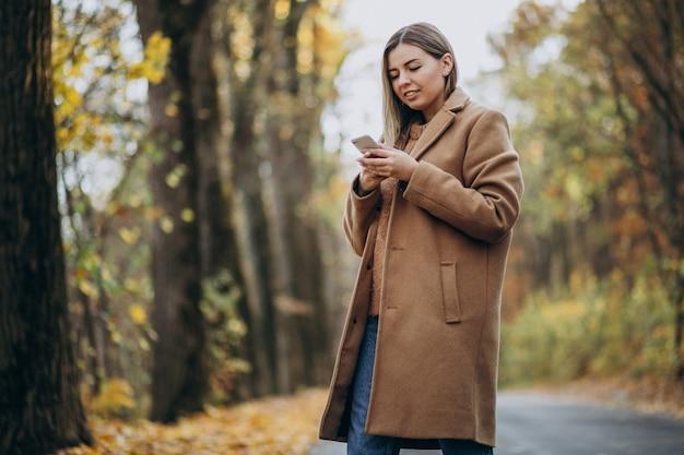 Mujer joven en abrigo de pie en la carretera en un parque de otoño