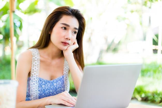 Mujer joven aburrida mientras uso portátil