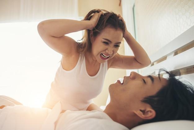 Mujer joven aburrida con su novio roncando