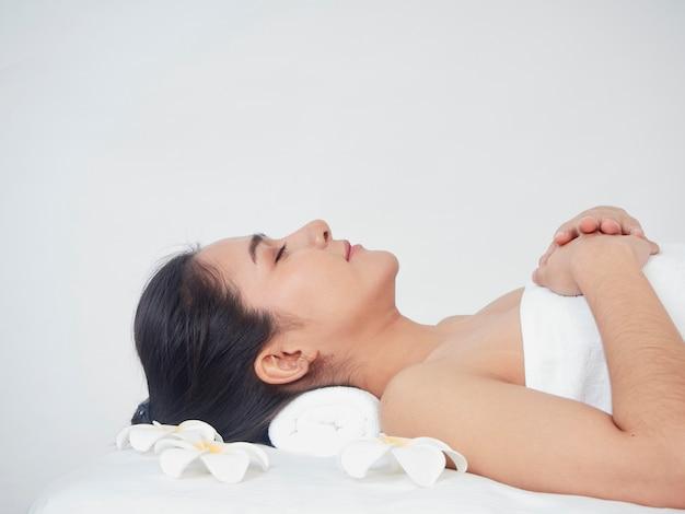 Mujer joven y accesorios de spa en mesa de masaje