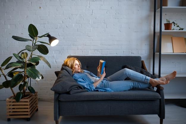 Mujer joven acostada en un acogedor sofá negro y leyendo un libro, salón en tonos blancos