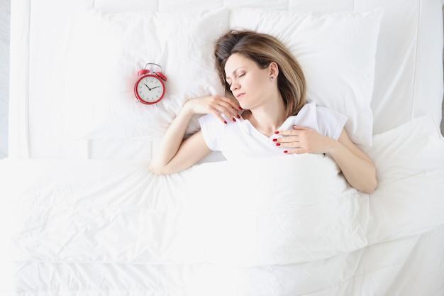 Mujer joven acostada en la cama cerca de la vista superior del despertador rojo. concepto de sueño saludable