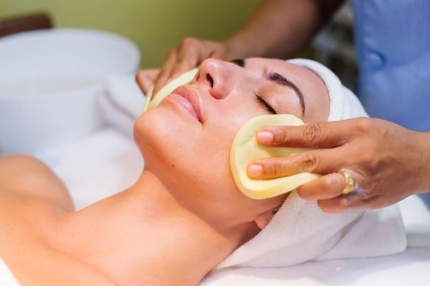 Mujer joven acostada sobre la mesa de la cosmetóloga durante el procedimiento de rejuvenecimiento