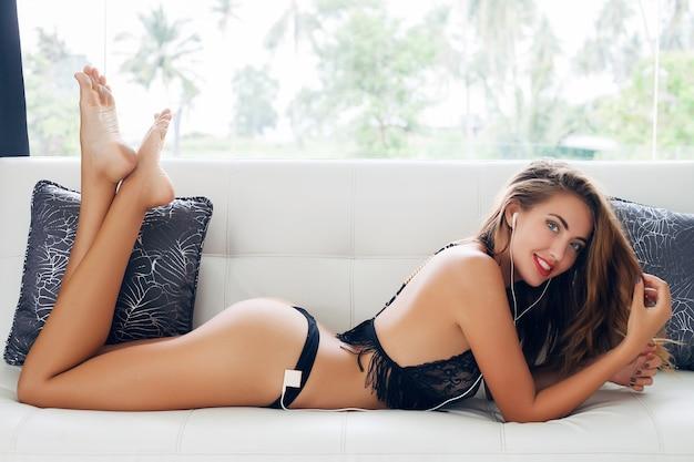 Mujer joven acostada sola en lencería seductora negra en un sofá blanco en una villa tropical escuchando música en el reproductor en auriculares sonriendo