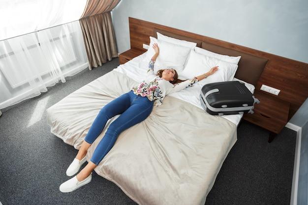 Mujer joven acostado en la cama de una habitación de hotel