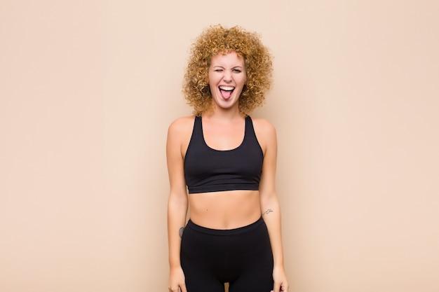 Mujer joven con actitud alegre, despreocupada, rebelde, bromeando y sacando la lengua, divirtiéndose concepto deportivo