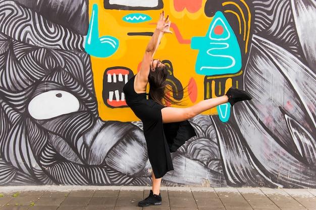 Mujer joven activa bailando contra la pared de graffiti