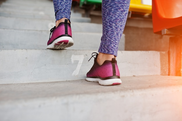 Mujer joven activa corriendo en las escaleras en el estadio.