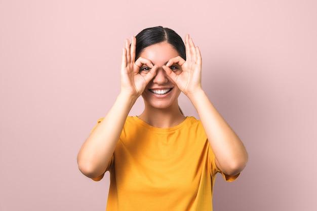 Mujer joven activa y enérgica imitando gafas