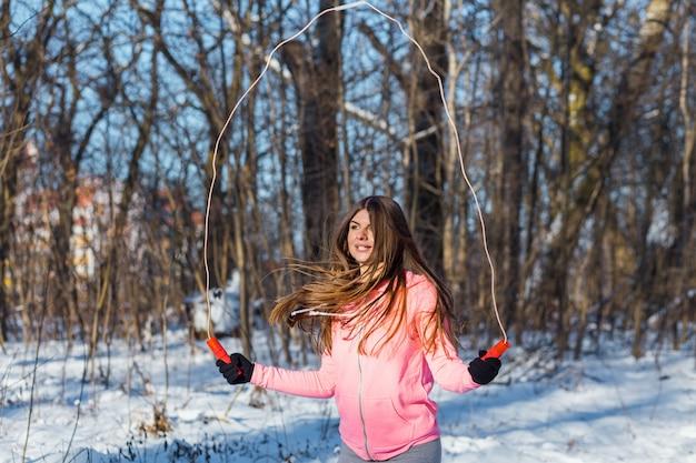 Mujer joven activa realiza un ejercicio con una cuerda de saltar