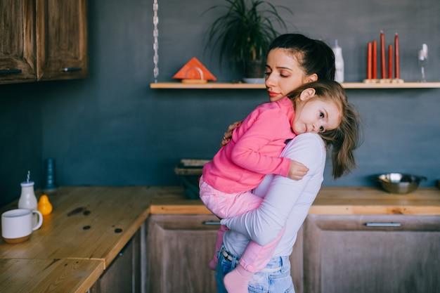 Mujer joven adorable que juega con su pequeña hija divertida en cocina. retrato de hermosa madre abrazando, llevando y mirando a su pequeña niña.