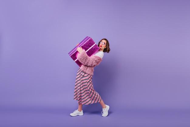 Mujer joven adorable en zapatillas blancas posando con caja actual. chica fascinante que besa la cara expresando mientras sostiene un gran regalo.