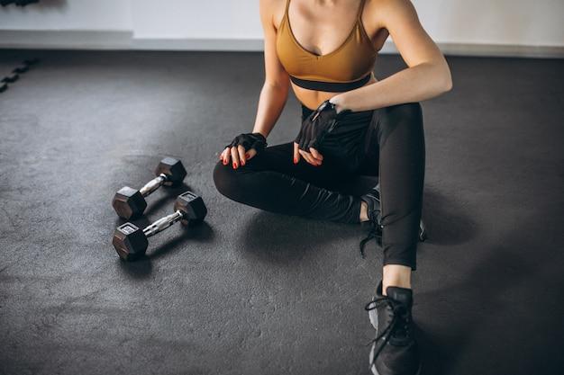 Mujer joven aercising en el gimnasio con pesas