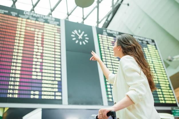 Mujer joven en el aeropuerto internacional mirando el tablero de información de vuelo comprobando el vuelo