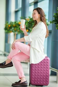 Mujer joven en el aeropuerto internacional con su equipaje y café para ir a esperar su vuelo