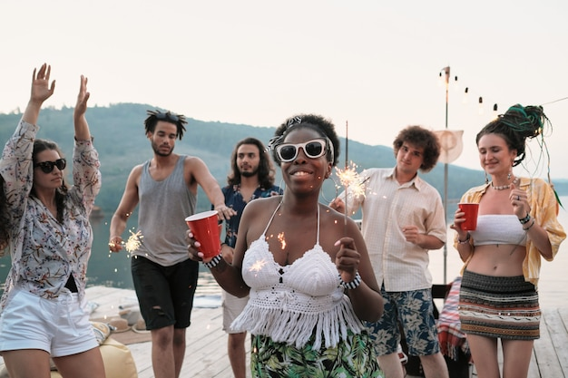 Mujer joven africana en gafas de sol con vaso de cerveza y bengalas sonriendo a la cámara mientras baila con sus amigos en la fiesta al aire libre