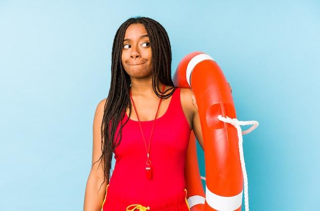 Mujer joven afroamericana salvavidas aislada confundida, se siente dudosa e insegura.