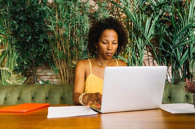 Mujer joven afroamericana sentada frente a plantas usando laptop