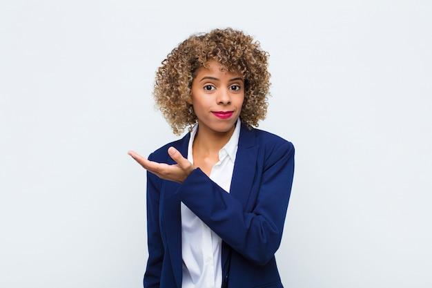 Mujer joven afroamericana sintiéndose confundida y desorientada, preguntándose sobre una explicación dudosa o pensamiento contra la pared plana