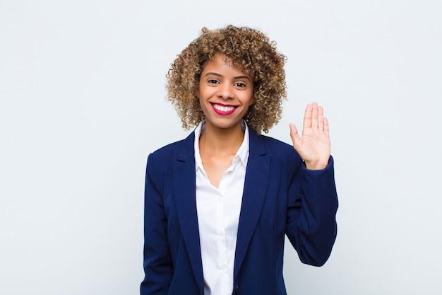 Mujer joven afroamericana sonriendo feliz y alegremente, saludando con la mano, dándole la bienvenida y saludando, o diciendo adiós contra la pared plana