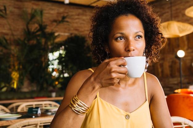 Mujer joven afroamericana tomando café de taza blanca