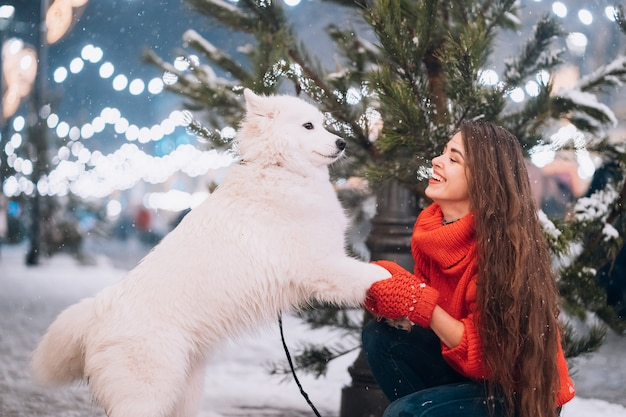 Mujer joven agachada junto a un perro en una calle de invierno