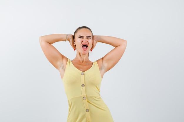 Mujer joven agarrando la cabeza con las manos mientras grita en vestido amarillo y parece agresivo