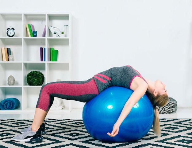 Mujer joven agotada que duerme en la bola azul de los pilates sobre la alfombra