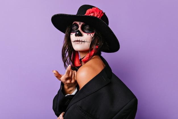 Mujer joven agraciada en sombrero negro que se coloca en la pared púrpura. chica morena despreocupada con maquillaje de halloween sonriendo suavemente.