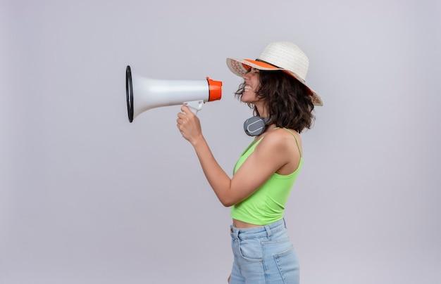Una mujer joven agresiva con el pelo corto en la parte superior de la cosecha verde en auriculares con sombrero para el sol hablando por megáfono sobre un fondo blanco.