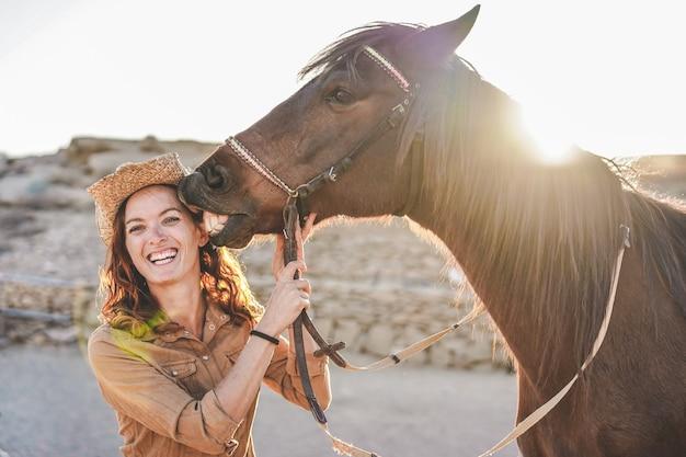 Mujer joven agricultor jugando con su caballo en un día soleado dentro del rancho corral - concepto sobre el amor entre personas y animales - centrarse en la cara de niña