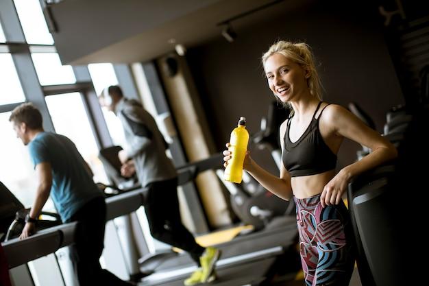 Mujer joven, agua potable, en, gimnasio, después, entrenamiento