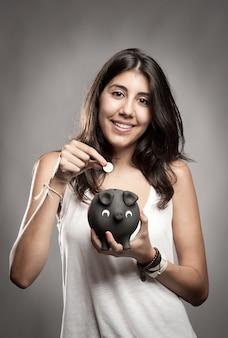 Mujer joven ahorrando dinero en una alcancía