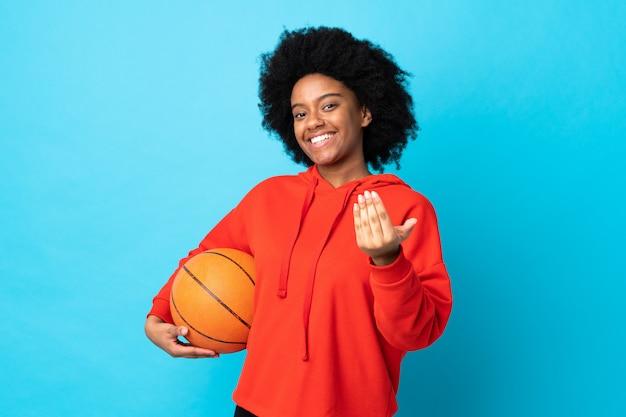 Mujer joven aislada en azul jugando baloncesto y haciendo gesto que viene