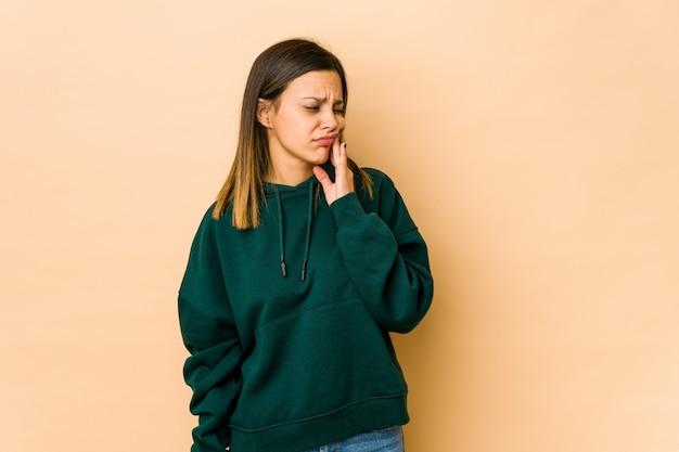 Mujer joven aislada en beige con un fuerte dolor de dientes, dolor molar.