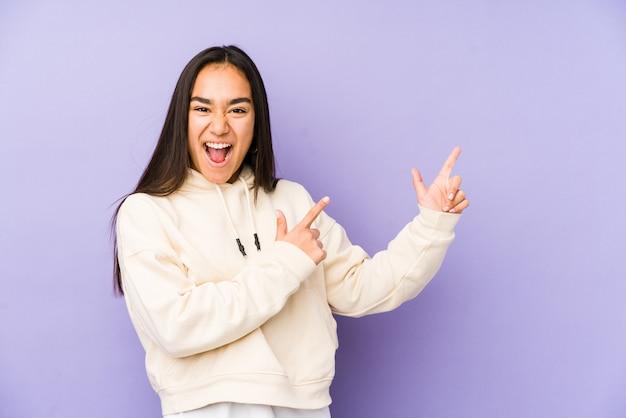 Mujer joven aislada en un fondo púrpura que señala con los dedos índices a un espacio de la copia, expresando la emoción y el deseo.