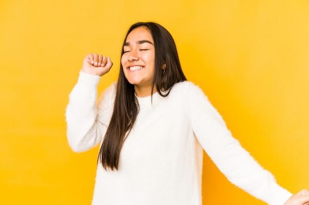 Mujer joven aislada en una pared amarilla bailando y divirtiéndose.