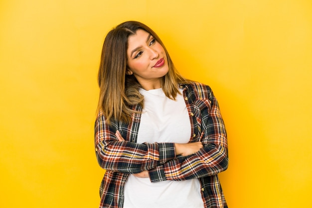 Mujer joven aislada en la pared amarilla soñando con lograr metas y propósitos