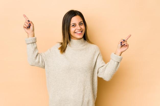 Mujer joven aislada en pared beige apuntando a diferentes espacios de copia, eligiendo uno de ellos, mostrando con el dedo.