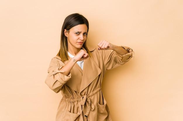 Mujer joven aislada en la pared beige lanzando un puñetazo, ira, luchando debido a una discusión, boxeo.