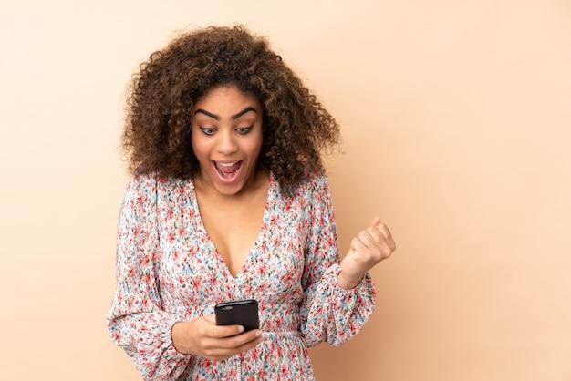 Mujer joven aislada en la pared beige sorprendida y enviando un mensaje