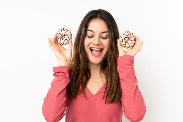 Mujer joven aislada en la pared de color rosa con rosquillas y sorprendido